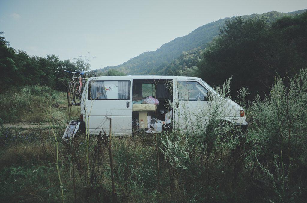 Un van blanc aménagé garé sur le bord d'une route de campagne